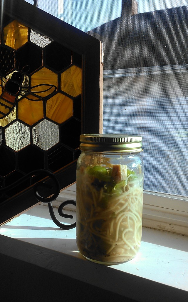 This batch of homemade chicken noodle soup contained chunks of chicken meat, celery, some leftover bacon, and pepper. Re-using an almond butter jar makes getting to work spill-free!